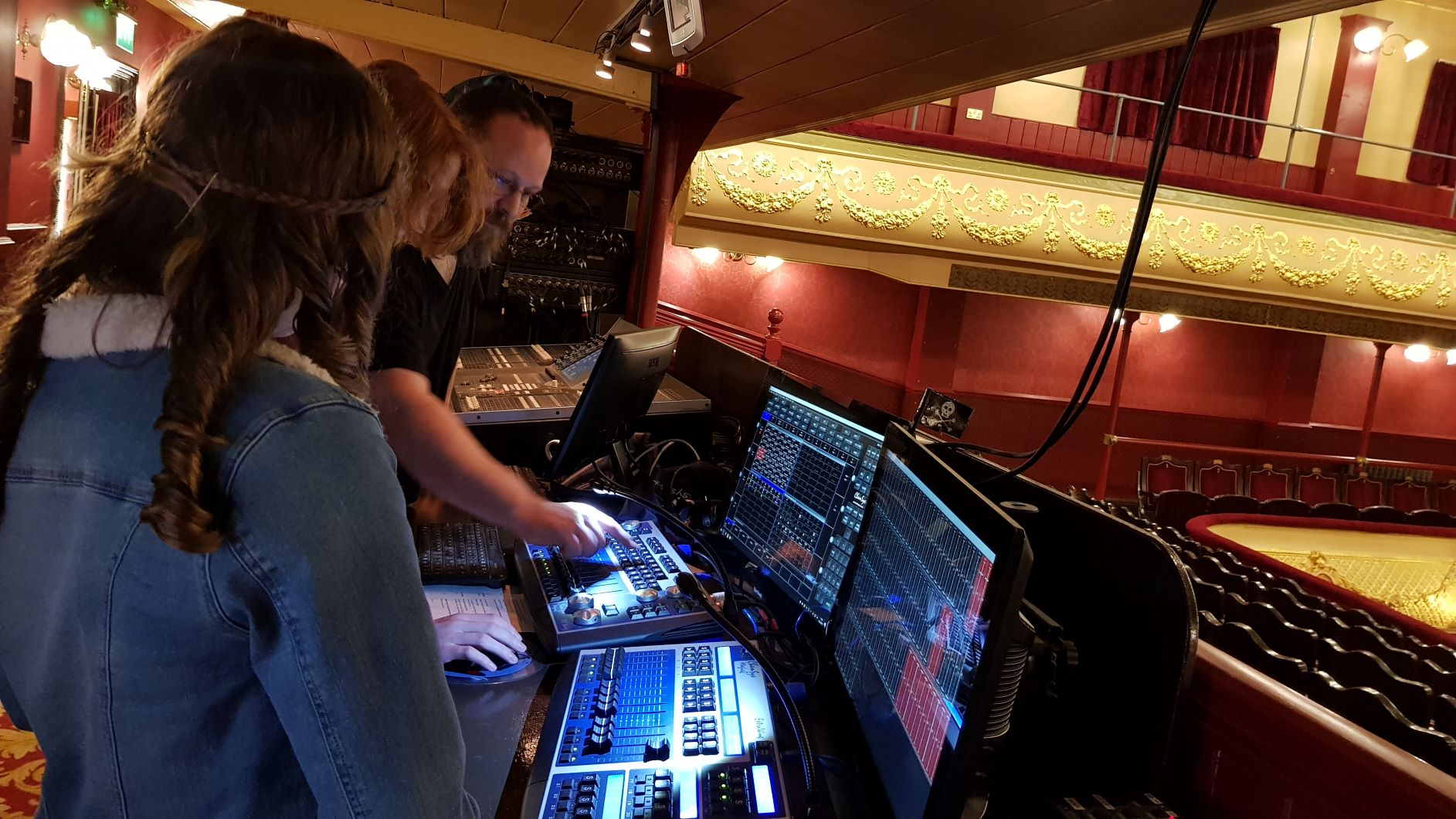 Two young people looking at lighting desk with technician
