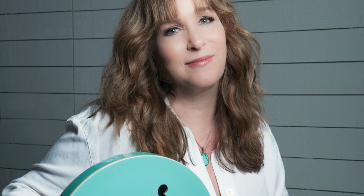 Gretchen Peters sits with a blue guitar.