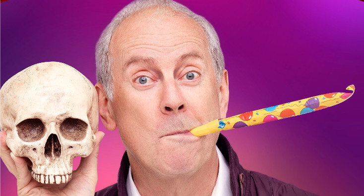 Gyles Brandreth holds a Yorick-style skull with a party horn in his mouth.