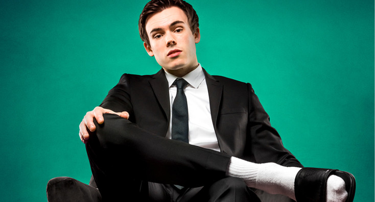 Rhys James sits cross-legged wearing a suit with pool sliders.