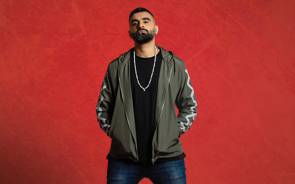 Tez Ilyas stands with his hands in his pockets. He is wearing jeans and a long chain over his black t-shirt. He stands against a red background