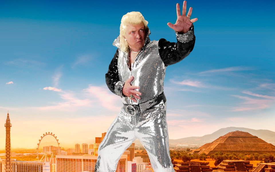 Clinton Baptiste stands in front of a Las Vegas skyline wearing a silver sequined jumpsuit.