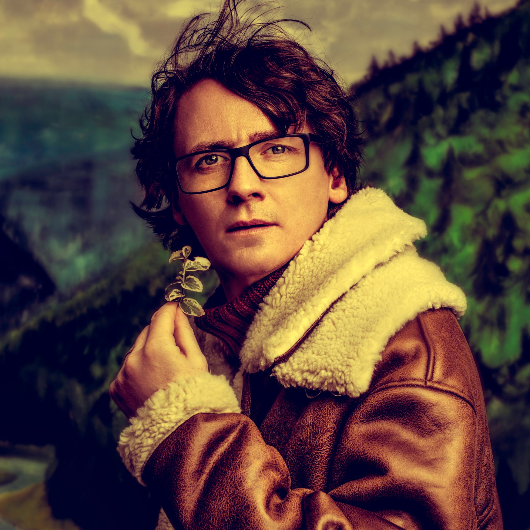 Ed Byrne wears a shearling jacked and holds a leaf as he is pictured on a mountainside.