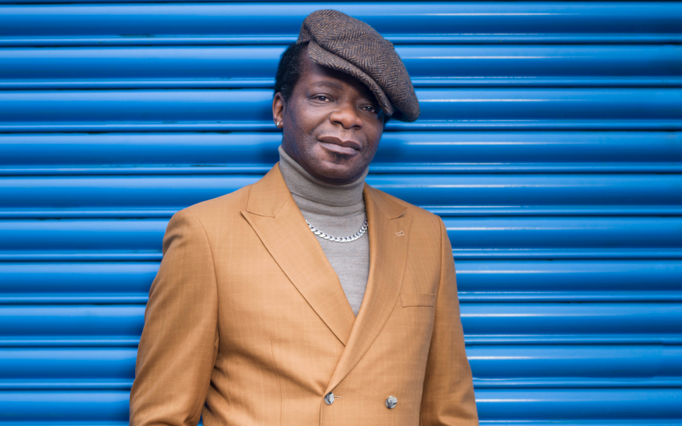 Stephen K Amos stands in front of a blue shutter door wearing a brown jacket, grey felt hat and silver chain.