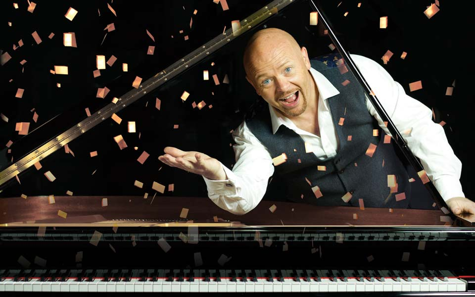 Comedian Jon Courtenay smiling under the lid of a grand piano with confetti falling