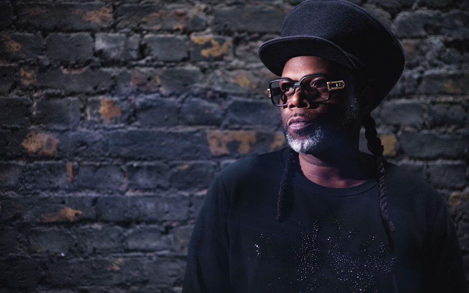 Jazzie B poses against a wall for the camera