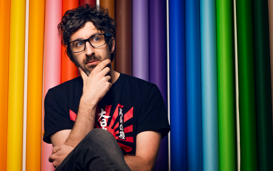 Mark Watson sits against a multi-coloured background with his legs crossed and hand on his chin as if he's musing.