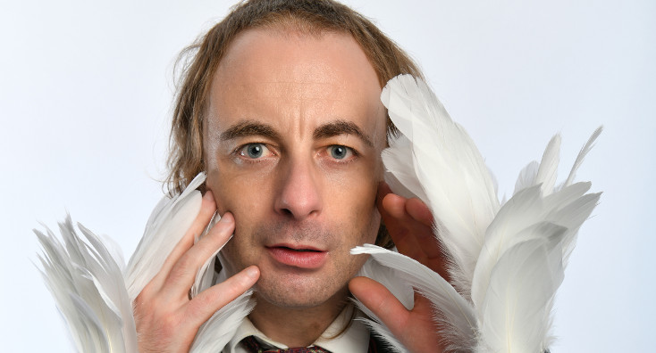 Paul Foot looks at the camera waving feathered hands in front of his face.