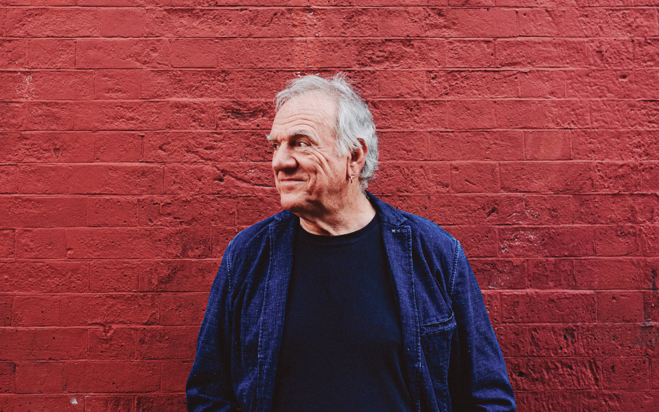 Ralph McTell faces off camera and stands in front of a red brick wall