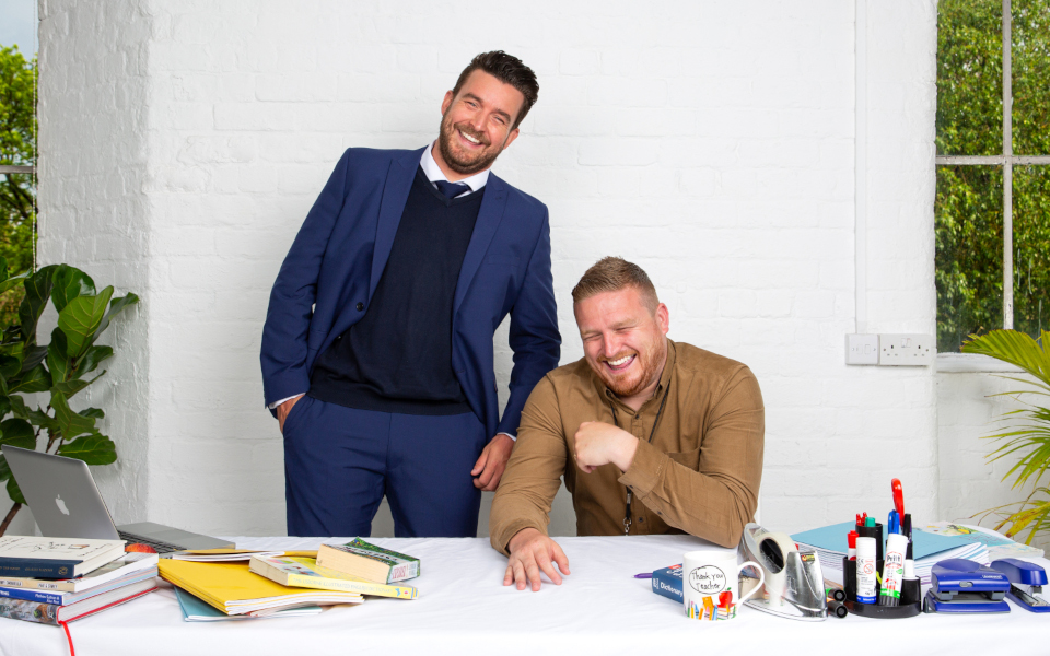 The two hosts of Mr Ps Podcast sat behind a desk covered in teacher miscellany