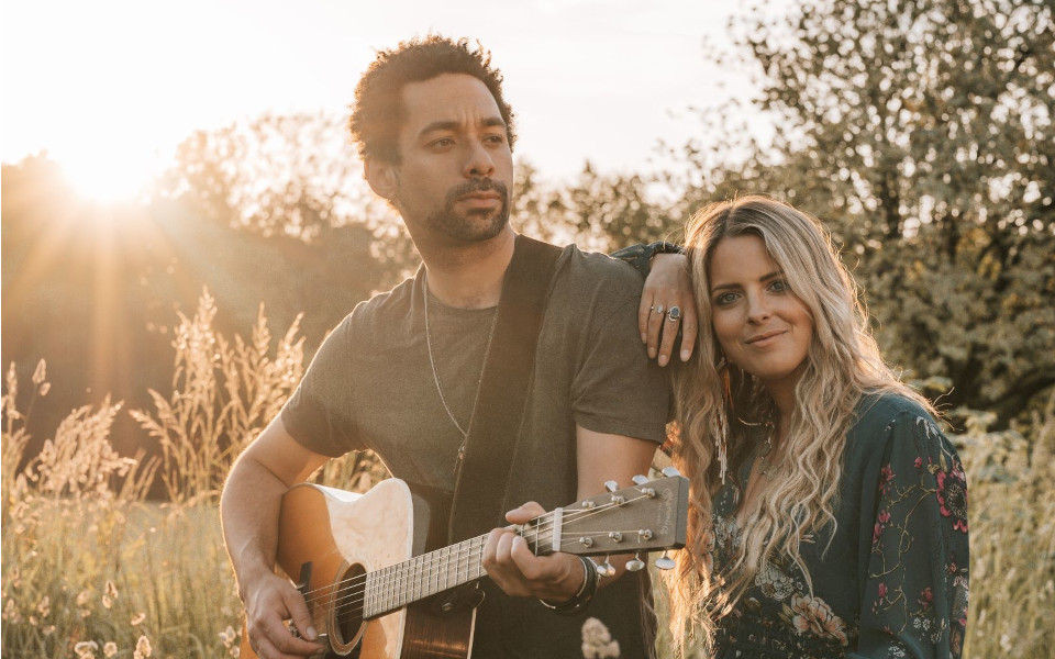 The musical duo, The Shires, a man and woman with a guitar in a field