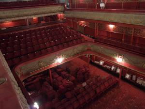 The auditorium of City Varieties Music Hall before the 2009 regeneration. There are rows of red theatre chairs with some pulled out and piled up.