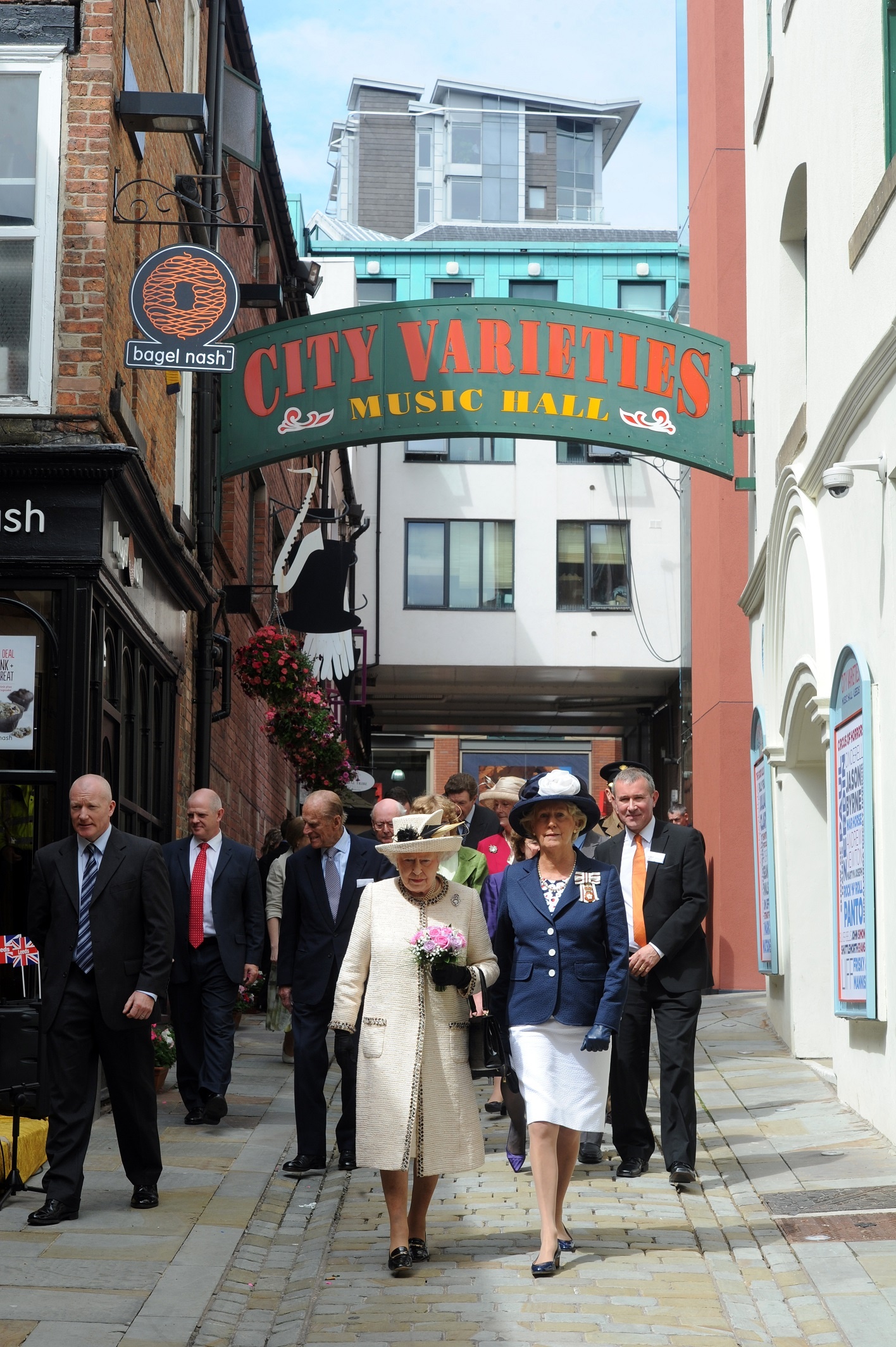 The Queen wearing a cream dress and hat followed by a group of people in suits walked down a narrow road. The sign above her reads City Varieties Music Hall.